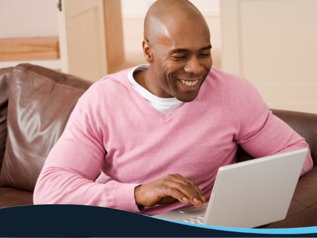 Bald man sitting on couch while looking at his laptop and smiling
