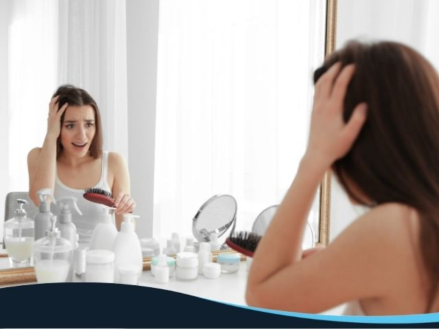 Woman holding a brush while looking in the mirror with a worried expressions